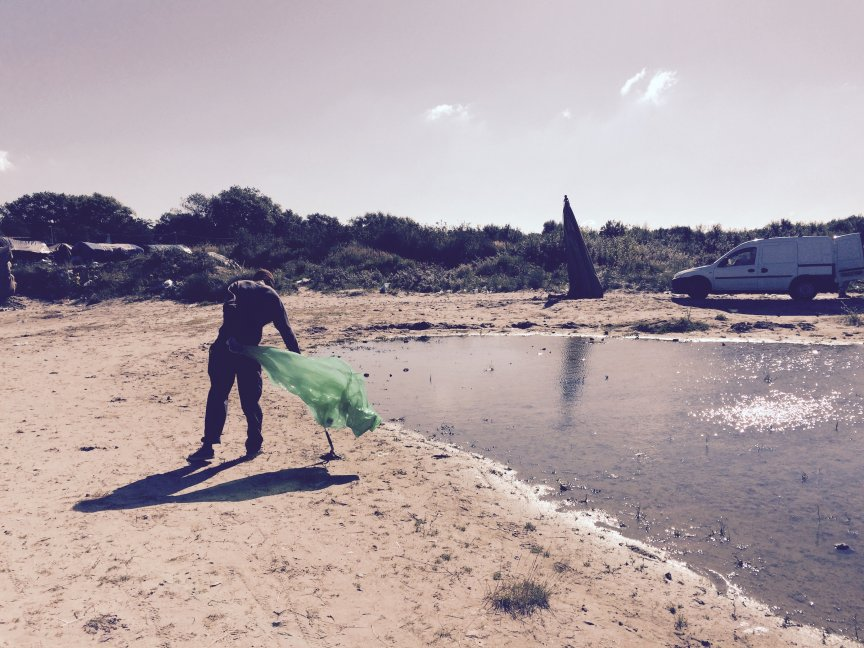 A refugee helping to collect rubbish