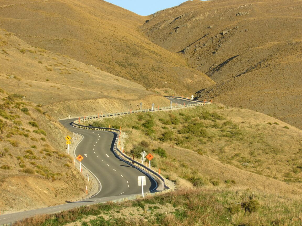 A photo of a long winding road going through mountains New Zealand road trip travel family long term